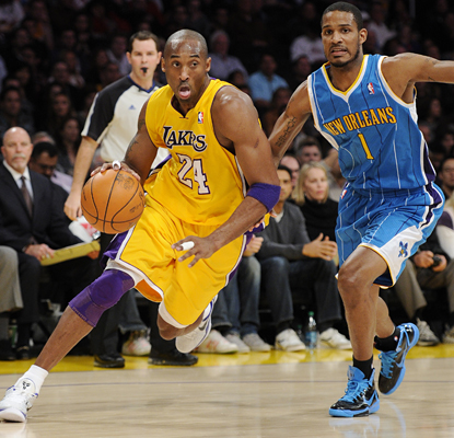 Kobe Bryant drives past Trevor Ariza as he works toward 25 points in the game and 26,712 for his career. (AP)