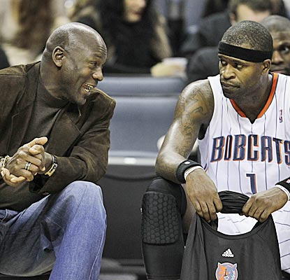 Bobcats owner Michael Jordan talks with Stephen Jackson in the second half of a game seen by only 1,000 spectators. (AP)