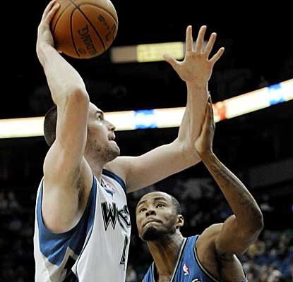 Timberwolves center Kevin Love puts up a shot against Wiz forward Rashard Lewis on Tuesday night. (AP)