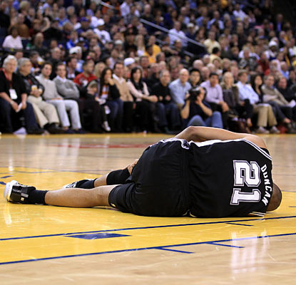 Although it looks like the worst, Tim Duncan suffers only a hyperflexed left knee and manages to return to action.  (Getty Images)