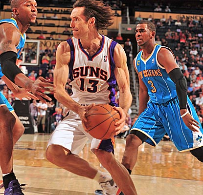 The Suns' Steve Nash looks to pass around David West, finishing with 15 assists in the win. (Getty Images)