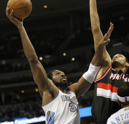 Nene goes to the basket past Trail Blazers center Chris Johnson as he works toward his 22 points and 10 rebounds. (AP)