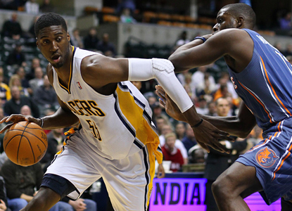 Roy Hibbert dribbles around Charlotte's Nazr Mohammed as he leads the Pacers to a win with 29 points. (US Presswire)