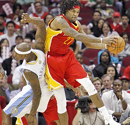 Jordan Hill rips down one of his six rebounds in front of Al Harrington in the Rockets' win. (US Presswire)