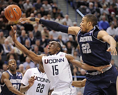 Connecticut's Kemba Walker drives past Georgetown's Julian Vaughn in the second half.  (AP)