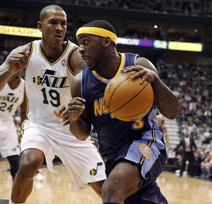 Ty Lawson works against Raja Bell and goes on to lead the Nuggets with 23 points in their win over the Jazz. (AP)