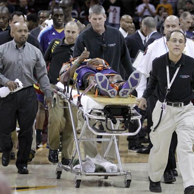 The Hornets' Chris Paul suffers a concussion and is taken off the floor on a stretcher. (AP)