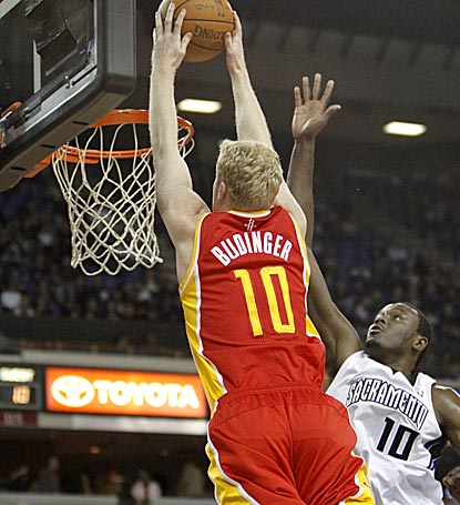 Houston's Chase Budinger skies for a dunk over Sacramento's Samuel Dalembert midway through the first quarter.  (AP)