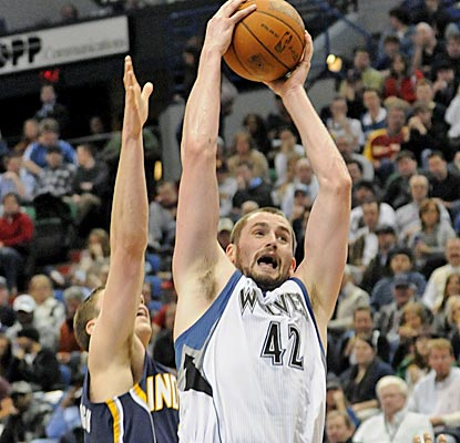 Kevin Love beats Tyler Hansbrough to a rebound, finishing with 21 boards on his record-breaking night. (AP)