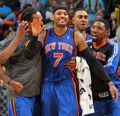 Carmelo Anthony is mobbed by his new teammates after he nails the winning jumper with 0.5 seconds left. (Getty Images)