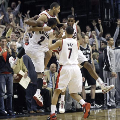 Nicolas Batum celebrates with teammates after draining the game winner against Tony Parker and the Spurs.   (AP)