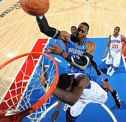 Back from a one-game suspension, Dwight Howard posterizes Sixers point guard Jrue Holiday in the Magic's win Monday. (Getty Images)