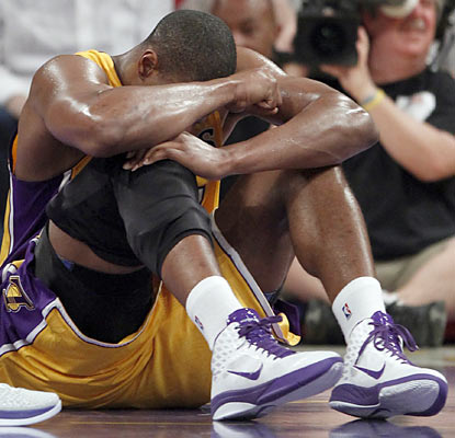 Andrew Bynum hyperextends his right knee in the second quarter. At halftime he tells Phil Jackson he's 'going to be OK.' (AP)