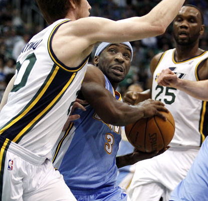 Ty Lawson works against the Jazz defense but leaves the game in the second quarter with a sprained ankle. (AP)