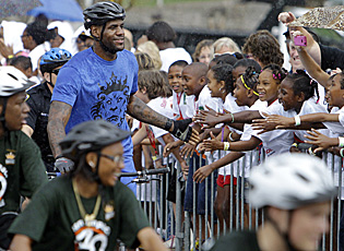 Heat superstar and Ohio native LeBron James greets children awaiting his arrival on an Akron bike path. (AP)