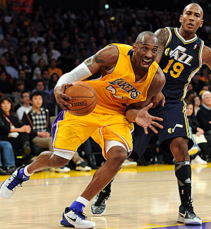 Battling a painful wrist injury, Los Angeles' Kobe Bryant blows by Utah's Raja Bell for two for his game-high 26 points.  (Getty Images)
