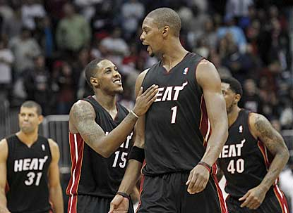 Chris Bosh (1) rescues Miami with a trey at the end of regulation and combines with Mario Chalmers (15) for 62 points.  (Getty Images)