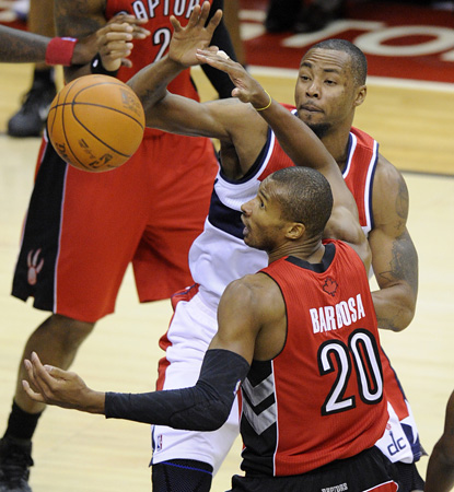 Rashard Lewis (center) fights for the ball for the Wizards.  His 15 points leads the team in their first victory in the season. (AP)