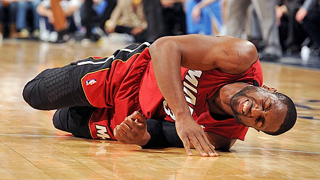 Wade grimaces in pain after injuring his ankle against the Nuggets on Friday. (Getty Images)
