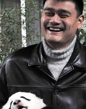 Retired NBA star Yao Ming holds a panda during a release ceremony at the Panda Valley nature preserve in China. (AP)