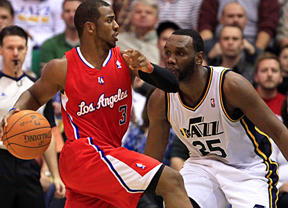 The Clippers' Chris Paul slips by the Jazz's Al Jefferson during the third quarter. (AP)