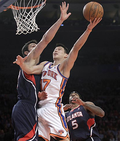 Jeremy Lin attacks the basket and uses his left hand to score a layup against Atlanta's Zaza Pachulia in the opening minutes.  (AP)
