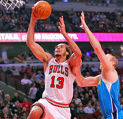 The Bulls' Joakim Noah drives past Chris Kaman of the Hornets during the first quarter.  (US Presswire)