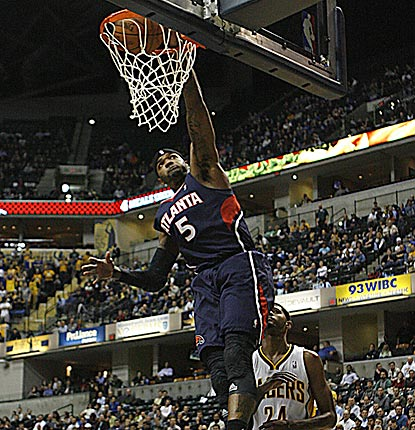 Danny Granger (rear) can only watch as Josh Smith dunks home two of his game-high 27 points.  (US Presswire)