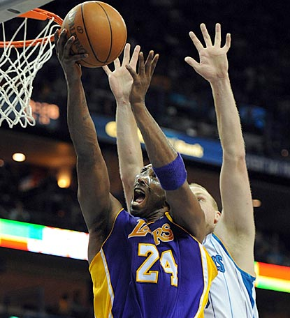 Kobe Bryant soars past Chris Kaman in the second half to help the Lakers win road overtime games on back-to-back nights.  (US Presswire)