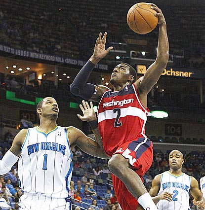 Trevor Ariza (left) can only watch as John Wall rises to the occasion while the Wizards are playing short-handed.  (US Presswire)