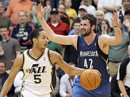 Kevin Love objects to a non-call while Utah's Devin Harris winds up with the ball during the overtime period.  (AP)