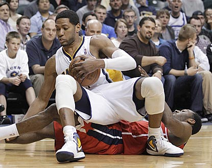 Danny Granger is pulled down to the court by John Wall during the second half.  (AP)