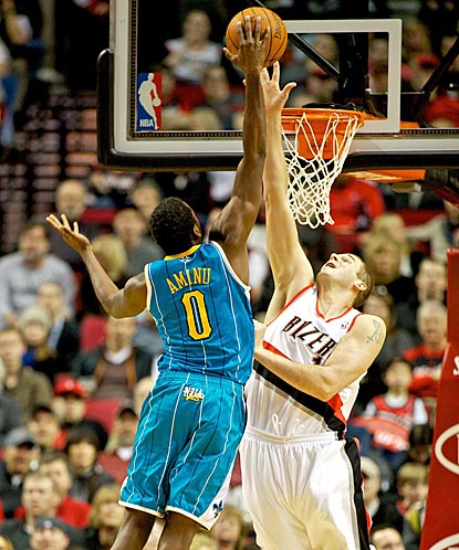 Hornets forward Al-Farouq Aminu (0) takes to the sky, but Joel Przybilla rejects his shot.  (US Presswire)