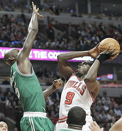Luol Deng shoots over Kevin Garnett in the second half, during which Deng scores 18 of his 26 points.  (AP)