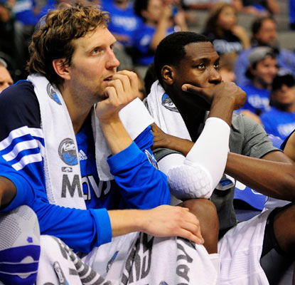 Dirk Nowitzki and Ian Mahinmi watch as the Mavs, champs last season, fall one game from being swept out of the first round.  (US Presswire)