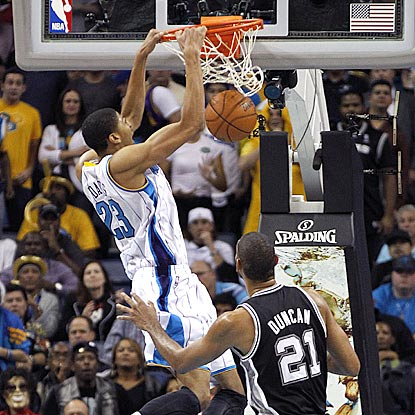 2012 top overall draft choice Anthony Davis dunks in front of 1997 top overall pick Tim Duncan in the second half.  (AP)