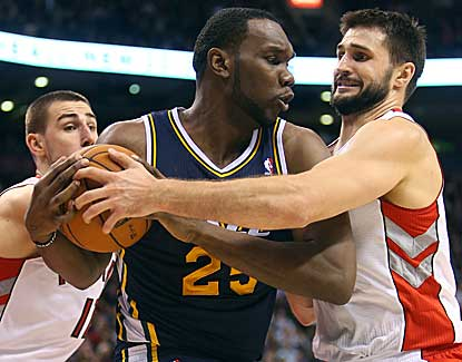 Utah's Al Jefferson, center, battles with Linas Kleiza and Jonas Valanciunas in the Jazz's win. (US Presswire)
