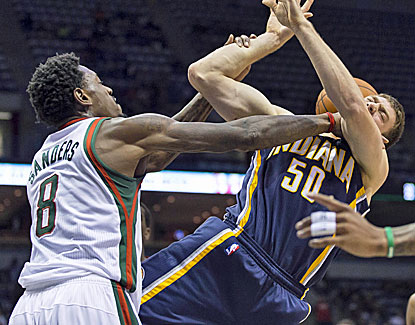 Milwaukee's Larry Sanders roughs up Indiana's Tyler Hansbrough, who scores 17 points in the game. (US Presswire)