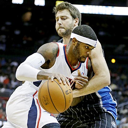 Josh Smith and the road-weary Hawks muscle their way past Josh McRoberts and the struggling Magic.  (AP)