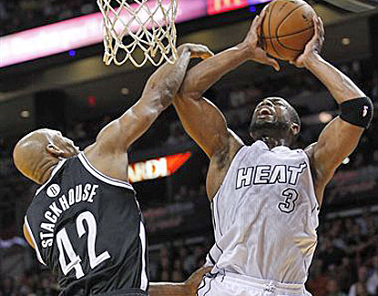 Dwyane Wade is in vintage form against the Nets, fighting to get to the basket against Brooklyn's Jerry Stackhouse. (AP)