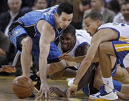 Orlando's J.J. Redick battles for a loose ball with Golden State's Festus Ezeli and Stephen Curry. (AP)