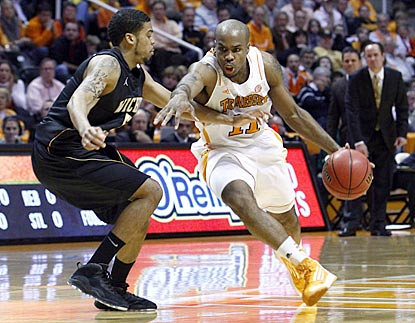 Trae Golden, driving here against Wichita State's Demetric Williams, helps spark Tennessee's offense out of dormancy.  (AP)