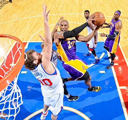 Kobe Bryant slashes his way past Spencer Hawes and the 76ers. He scores at least 30 points for the sixth consecutive game.  (AP)