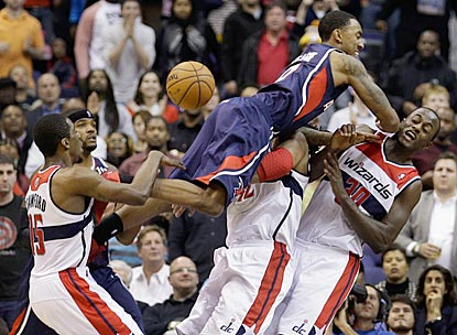 Atlanta's Jeff Teague nearly wipes out Washington's Nene (42) and Earl Barron (30) and earns a charging foul.  (Getty Images)