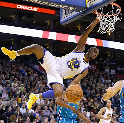 Carl Landry hangs on after dunking during the fourth quarter, and the Warriors hang on to beat the Hornets.  (Getty Images)