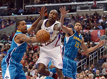 Clippers guard Jamal Crawford makes a pass while Dominic McGuire (left) and Anthony Davis try to defend.  (Getty Images)