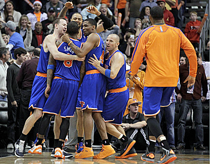 Knicks players huddle around J.R. Smith after he hits a 21-footer at the buzzer to beat the Suns. (AP)