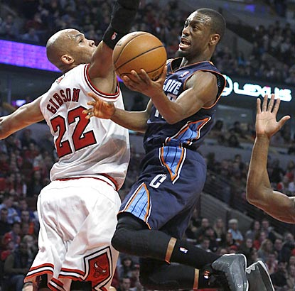 Kemba Walker, who winds up leading Charlotte with 18 points, drives around Chicago forward Taj Gibson during the first half.  (AP)