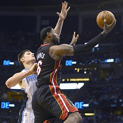 Orlando's Nikola Vucevic (left) grabs a team-record 29 rebounds, but LeBron James scores eight points in OT to rescue Miami.  (AP)