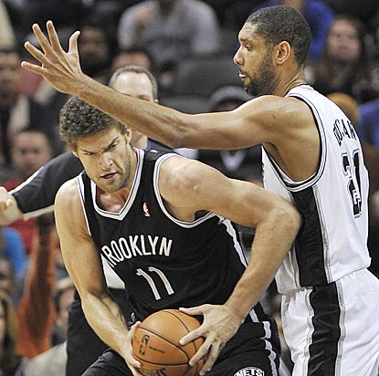 Tim Duncan and the Spurs don't give Brook Lopez and the Nets a lot of space to operate their offense.  (AP)